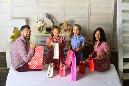 Man, woman and adorable children with gifts at home. Happy family and shopping concept. Mother, father and daughters with shopping bags and packs. Family with cheerful faces open presents at home.