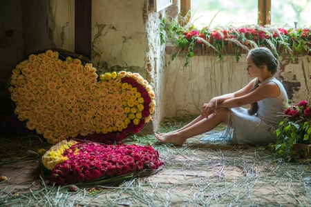 Young girl with flower bouquets, floral arrangement, garlands in old house. Hearts, roses, love, romance. Valentines day concept. Floristic, floral or flower shop.