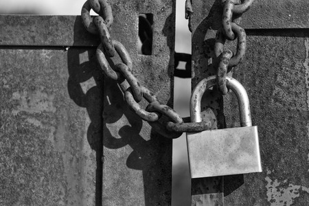 Padlock with shackle and locking mechanism closeup one portable lock on chain on unpainted rusty metal gate doors outdoor on blurred background 版權商用圖片