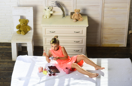 Little girl applying make up in room with toys. Makeup and kids fashion concept. Kid wears bright dress and holds cup in room with teddy bears. Girl with serious face drinks tea on bed in childroom.