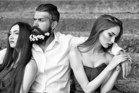 Hombre guapo en camisa blanca con flores de diente de león en la barba con dos jóvenes mujeres bonitas en vestidos violetas en escaleras pedregosas día soleado al aire libre Foto de archivo