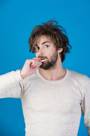 Happy man with beard grooming on blue background. Man with disheveled hair in underwear brush teeth. Stock Photo