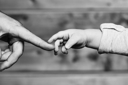 Closeup of two touching hands of small baby boy holding finger of male father as symbol of family love and trust on blurred wooden background, horizontal picture