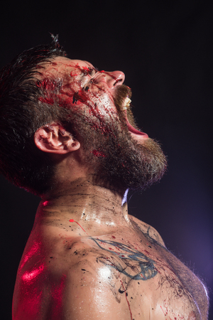 Bearded hipster with red blood on face, tattooed chest. Man with beard shout with anger on black background.