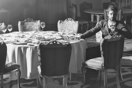Handsome young man with beard and blond hair drinks wine from glass sitting at table with leftovers or residues food on dirty plates after banquet dinner in restaurant