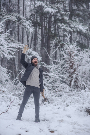 Bearded man with axe in snowy forest. Temperature, freezing, cold snap, snowfall. Man lumberjack with ax.