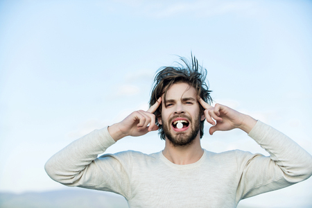 man with pill in mouth has uncombed hair in morning outdoor on sky background, health and medicine, handover and headache, drug, cold and flu, insomnia Stock Photo