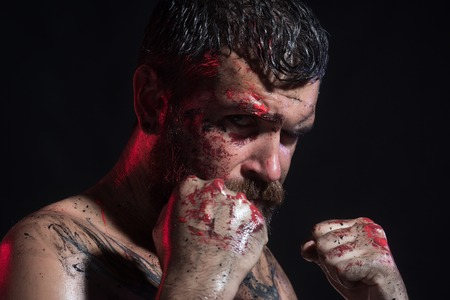 Sport, boxing, fighting. Man in fight position with blood paint on face, fists.