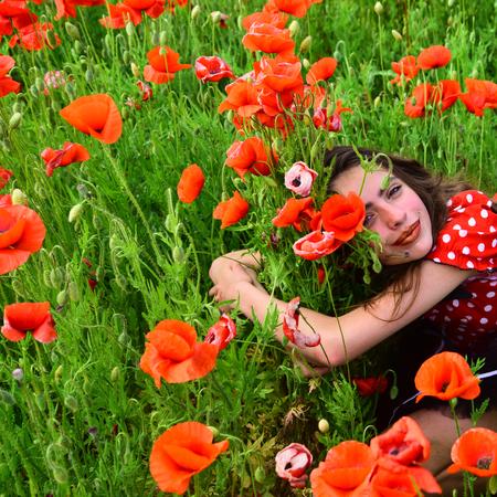 Woman in poppy flower field, harvest. pretty woman with poppy red flower