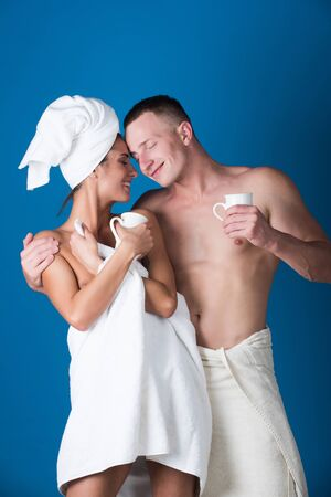 wife or happy girl near man in terry towel hold coffee, tea cup on blue background, family and morning, couple in love