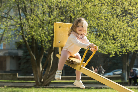 Childhood, activity, lifestyle. Kid on teeter totter outdoor. Girl sit on seesaw on sunny day. Balance, equilibrium, harmony. Child have fun on playground.