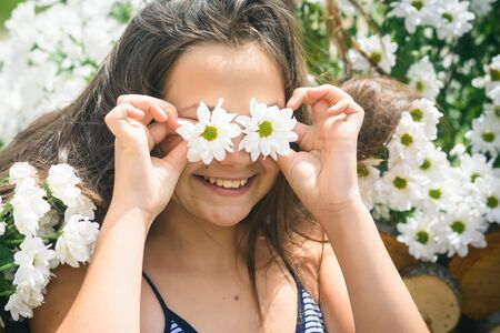 Camomile flowers blossoming and cute girl. Camomile bloom and small child.