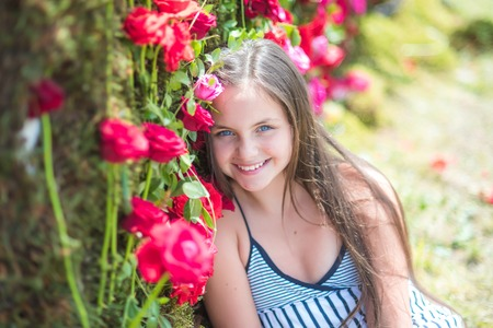 Little child with flowers, spring. Girl smile with red roses, beauty. Floristic, floral decor, design, flower shop. Beauty, spring, summer season. Valentines day, holiday celebration concept. Stockfoto - 95307328