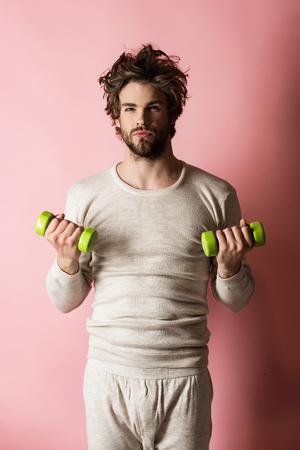 Man workout after wake up, fitness. Sportsman, man on pink background. Athlete in underwear training with barbell. Energy and sport success, coach. Morning exercise and healthy lifestyle.