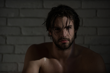 sexy man with wet hair and muscular body in bath or shower at brick wall, hygiene and spa Archivio Fotografico