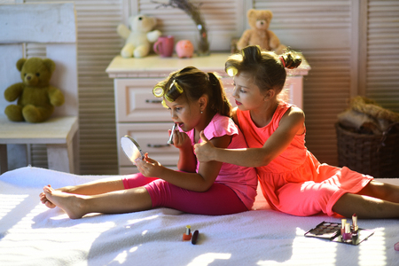 Little girls with curlers play with makeup accessories in childroom. Beauty and kids fashion concept. Children smile and sit on bed with lipstick and mirror. Girls do makeup sitting in room with toys.