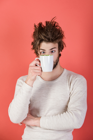 Insomnia, refreshment and energy. Cold and flu, single. Surprised guy with tea cup on red background. Morning with coffee or milk. Man with disheveled hair drink mulled wine. Stock fotó