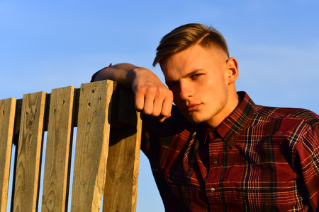 man rest at wooden fence, tired. carpenter or woodworker in sunrise. future looking and thinking, memories. summer holiday and travel. Man thinking and dreaming in sunset. Stock Photo