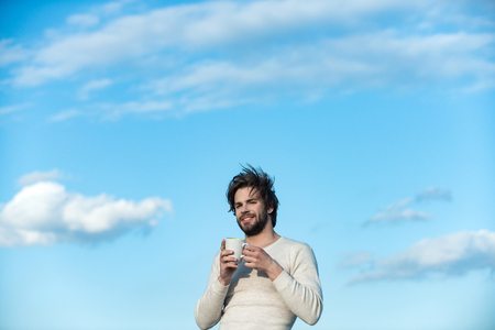 Cold and flu, single. Happy guy with tea cup on blue sky background. Man with disheveled hair drink mulled wine. Insomnia, refreshment and energy. Morning with coffee or milk.