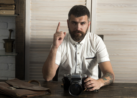Bearded man with camera and raised finger up at desk. Got idea concept. Discovery, imagination, innovation, inspiration. Photographer, journalist, journalism. Reklamní fotografie