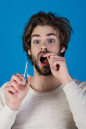 Single with uncombed hair. Morning, hair care, everyday life. Barber and hairdresser, male fashion. Man with disheveled hair grooming in morning. Man trimming nose hair with scissors and tweezers.