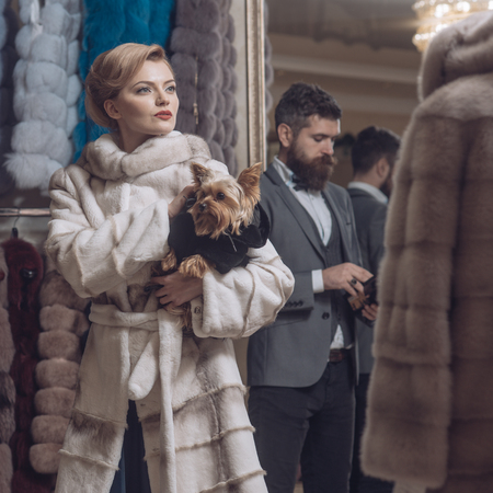 Woman in fur coat with man, shopping, seller and customer. Date, couple, love, man and woman. Couple in love among fur coat with dog, luxury. Fashion and beauty, winter. Purchase, business, moneybags.