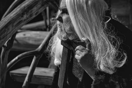 長い銀色の髪と毛皮のコートでひげを持つ老人ドルイドは、屋外の木製の家の背景に大きな鋭い斧を保持
