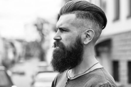 Handsome young stylish hipster man with long beard in grey shirt standing outdoor Stok Fotoğraf