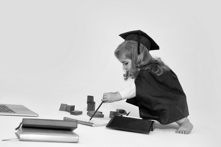 Little boy child in graduation squared cap and black mantle sitting and drawing by pencil in copy book near box with colored pencils wooden blocks diaries and open notebook isolated Imagens - 96488084