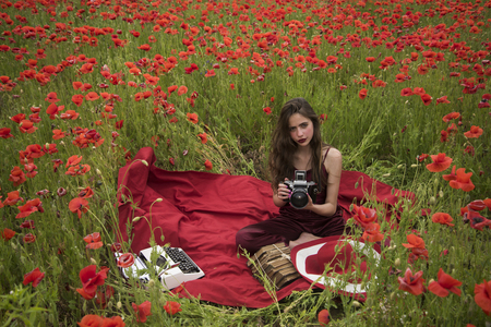 Poppy, Remembrance or Anzac Day. Opium poppy, agile business, ecology. Drug, narcotics, opium, woman with typewriter, camera, book. Woman writer in poppy flower field. Journalism and writing, summer.