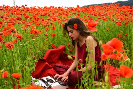 Drug, narcotics, opium, woman with typewriter, camera, book. Journalism and writing, summer. Opium poppy, agile business, ecology. Poppy, Remembrance or Anzac Day. Woman writer in poppy flower field. Reklamní fotografie