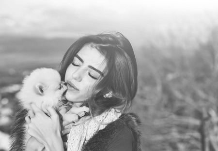 pretty girl young beautiful woman in fur waistcoat and scarf holds cute small dog pet in hands outdoors on natural background