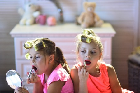 Little girls do makeup sitting in room with toys. Children sit on bed with lipsticks and look in hand mirror. Girls with curlers play with makeup accessories. Beauty and kids fashion concept.