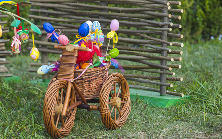 Spring, easter season, festival. Wicker tricycle with basket on grass. Happy easter celebration. Small bicycle with easter eggs. Stock Photo