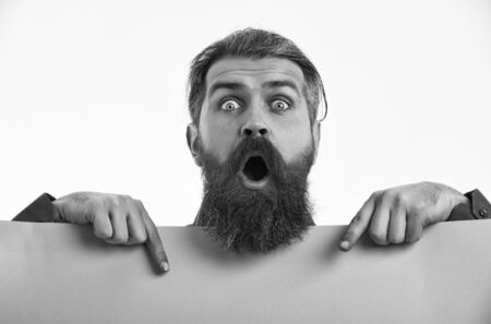 bearded man, long beard, brutal caucasian hipster with moustache on surprised face, unshaven guy with stylish hair getting haircut with green paper sheet isolated on white background, copy space