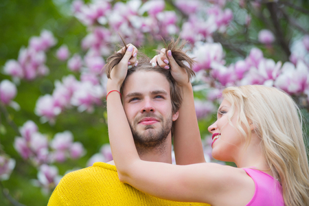 Beautiful young loving couple embracing in blossom spring garden