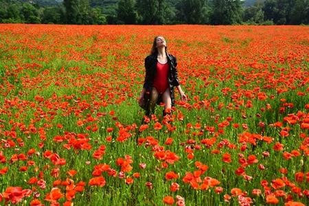 夏の間、ケシ畑の真ん中にいる女性