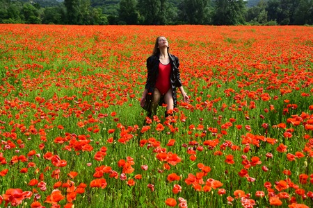 Woman in the middle of poppy field during summer