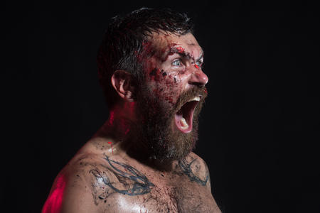 Bearded man shout with horror on brutal face. Hipster with bloody beard, tattoo on chest on black background. Halloween holidays celebration. Magic, enchantment, witchcraft. Wizard, sorcerer, warlock. Stock Photo