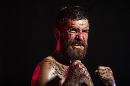 Bearded man with blood paint on angry face. Hipster in fight position with fists on black background. Sport, boxing, fighting. Power, might, magic. Halloween, holidays celebration.