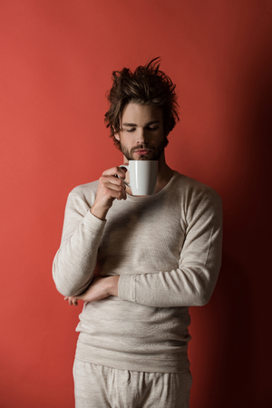 sleepy man with disheveled hair drink coffee in morning on red background, flu and cold, hangover and insomnia, energy