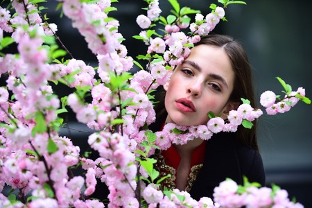 Young woman at cherry tree with pink flowers, beauty. Girl with blossoming sakura on spring day. Easter holiday celebration concept. Spring nature, beauty, new life, environment.