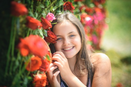 Valentines day, holiday celebration concept. Little child with flowers, spring. Beauty, spring, summer season. Girl smile with red roses, beauty. Floristic, floral decor, design, flower shop.