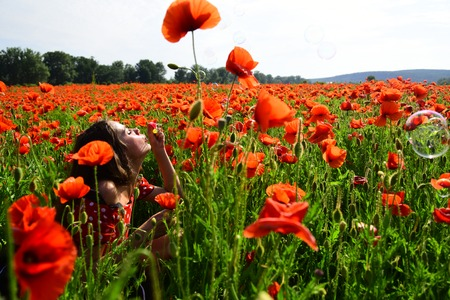 Woman blow bubble in poppy field, dreams, wishes. Summer, spring, poppy flower. Opium poppy, youth, freshness, ecology, woman. Drug, opium, narcotics, carelessness. Poppy, Remembrance day, Anzac Day.