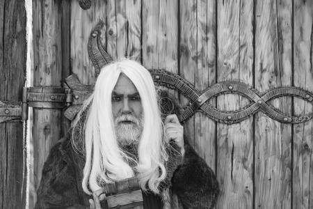 長い灰色の髪とひげの長い男は、鉄の装飾と木の背景に屋外で手で木製のマグカップで深刻な顔に