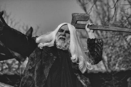 Brutal druid old man with long silver hair and beard in fur coat with axe in hand on blue sky background 写真素材