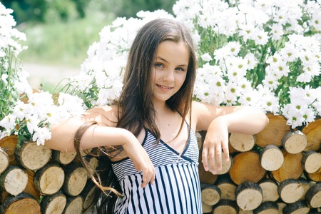 Little child at wooden fence with camomile flowers, beauty. Girl pose with daisy flowers on sunny day, spring. Beauty, look, hair. Spring, summer, romance.