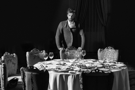 Handsome young man with beard and blond hair stands over table with leftovers or residues food on dirty plates after banquet dinner in restaurant on dark background Reklamní fotografie
