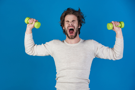 Sportsman, shouting man on blue background. Athlete in underwear training with barbell. Man workout after wake up, fitness. Morning exercise and healthy lifestyle. Energy and sport success, coach. Reklamní fotografie