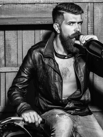 Bearded man hipster biker with beard and moustache handsome stylish male in leather jacket drinks from bottle on motorcycle on wooden background Stok Fotoğraf